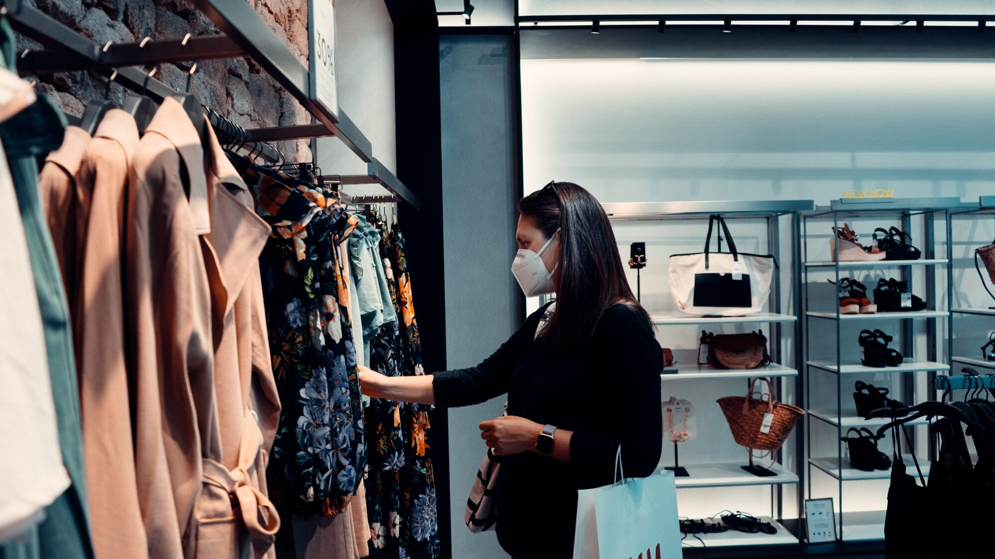 An image of a woman clothes shopping with a mask on
